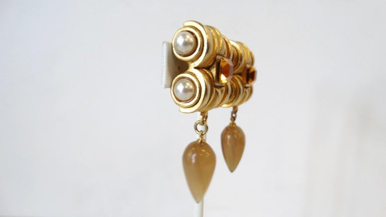 Your Perfect Earrings For Fall Have Arrived! A gold plated top resembling an Ionic Greek column features four pearls and an Amber rhinestone in the center. Hanging off the structured clip on closure top is a tear drop Amber Crystal. Unsigned.