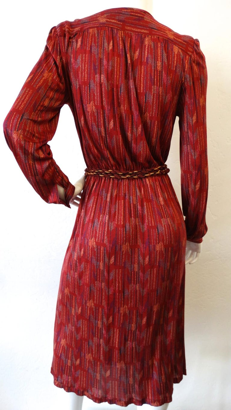 Your Perfect Fall and Holiday Dress Has Arrived-with our silk Missoni wrap dress circa 1970s! Featuring a rich cherry red color which stands out against the unique and colorful abstract tribal inspired print. Features cuff sleeves and strong