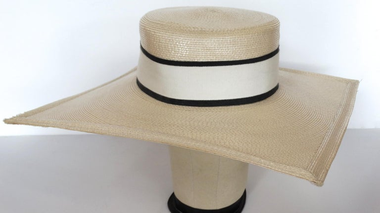 Say Hello To The Most Amazing YSL Hat! Circa early 1970s, this hat is a classic boater with a unique square shape brim. Features a large white ribbon with black trim around the crown. Two removable fascinators are included on the interior trim for a