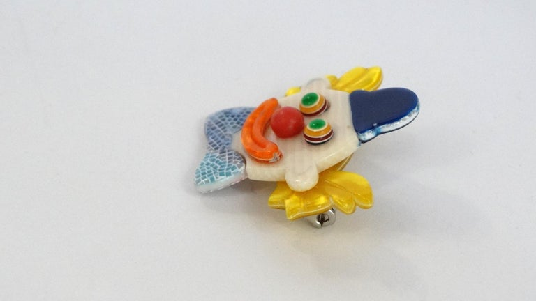 The Cutest Accessory To Add To Your Next Look! Circa 1970s, this clown brooch features an array of vibrants colors and rainbow striped eyes. Small tiles in shades of pearly blues and greys create the effect of layered snake skin on the bow tie. 100%