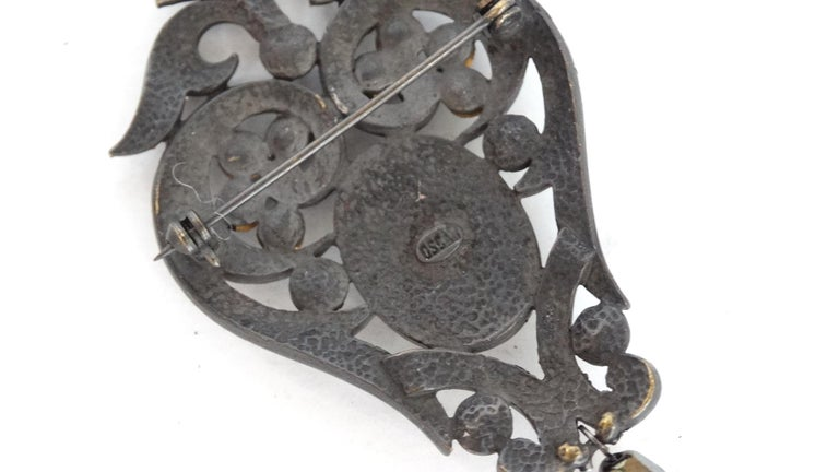 Everyone Needs An Elegant Brooch! A brass plated decorative setting is accented with crystal and black rhinestones. Features a detailed ivory Victorian style woman against a black background, and a hanging beaded accent. Signed Oscar but designer is