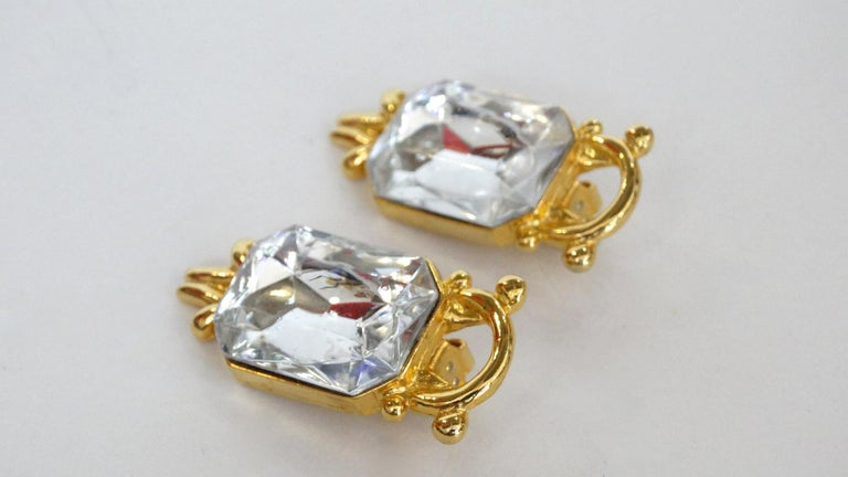 Show Some Sparkle With These Paolo Gucci Earrings! Circa 1980s, these gold plated earrings features a decorative setting which frames a large crystal. Clip-on closures and signed Paolo. The perfect statement earring to add to your next