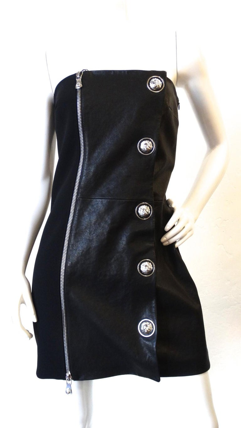 The Sexiest Cocktail Dress Is Here! Circa late 2000s, this dress is designed by Anthony Vaccarello who created a capsule collection for Versus Versace from 2014-2016. This mini strapless dress is half leather and polyester. Features a large silver