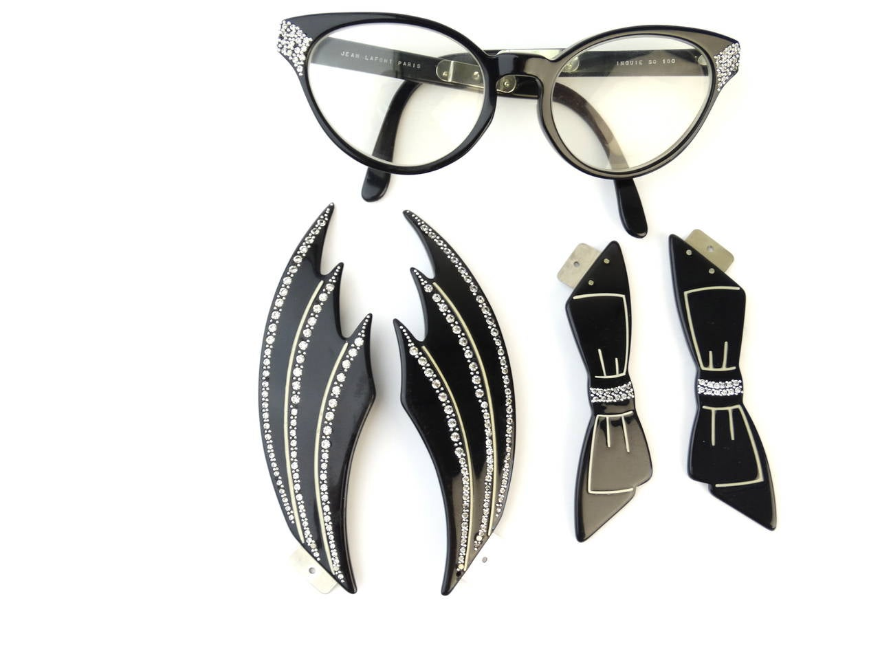 Featured a beautiful and unique pair of Jean Lafont eyeglasses circa 1960s. These eyeglasses have a unquie feature you have the option of wearing them as a classic cat eye frame or attach a pair of rhinestone wings or bows to the arms. Super