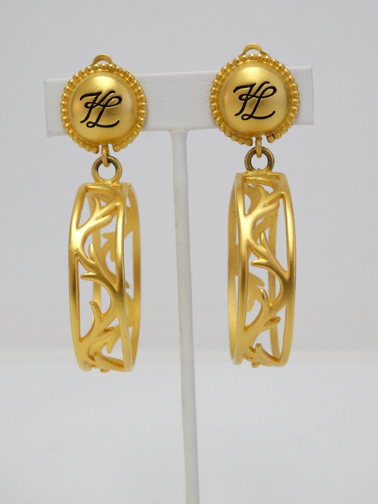 These are a beautiful style of hoop, great design in the center of the earring.  Signed KARL LAGERFELD~KL hoops, these are clip ons. They dangle almost 3 inches long and almost 2 inches wide. Gold plated. If you are a fan of a good hoop earring,