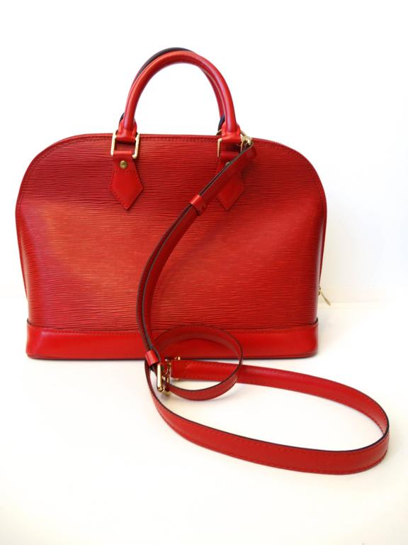 LOUIS VUITTON Vintage Epi Alma PM in Castilian Red. This is a stunning bowler style tote that is created out of Louis Vuitton signature textured epi leather in red. The bag features strong cowhide rolled leather handles and trim with brass hardware
