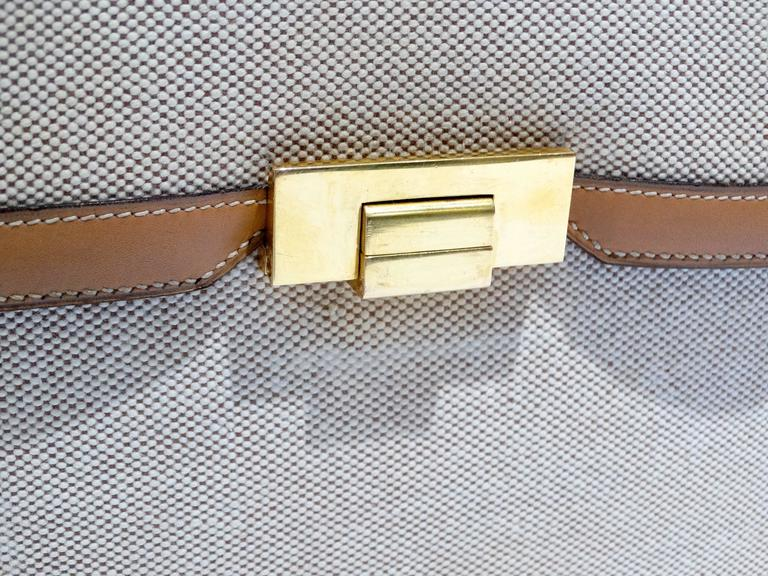 Beautiful 1960's box canvas handbag by Hermes with beige canvas linen body and tan leather trim. Bag features a single rolled leather handle and the signature Hermes flap top closure with a gold tone metal clasp to fasten. It features an accordion