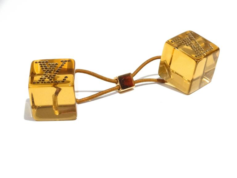Add some fun to your hair with this adorable Louis Vuitton Amber Resin Hair Cube! They feature colored and clear resin with the Louis Vuitton logo in crystals on each cube, makes for a perfectly unique hair accessory! Great for evening or day!