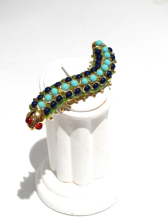 "A fun Kenneth Jay Lane Caterpillar brooch circa 1995 in green enamel, glass ruby cabochons, plastic lapis lazuli and turquoise cabochons. Signed KJL. You can also reference this piece in Kenneth Jay Lane's ""Faking It"" book. This piece will come in"