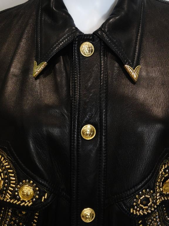 This iconic 1990's cropped black-leather motor cycle jacket is a wonderful example of Gianni Versace's genius. Loving the overload of gold and silver -studs and Medusa head buttons which for Versace reflected beauty, art and philosophy. The cropped