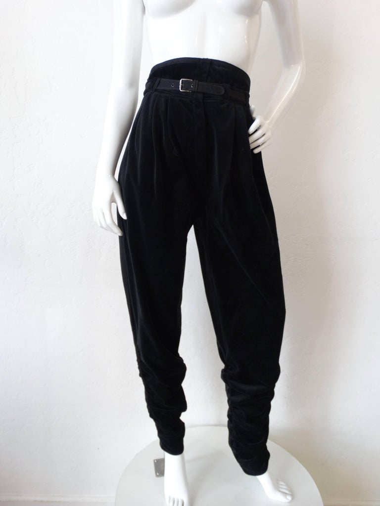 Up your fall wardrobe game in our 1980s Gianni Versace pants! Made of a luxurious midnight black velvet with grosgrain trim accents and matching belt. Super high waisted rise with flattering tapered legs. Velvet gathered around the ankles and legs,