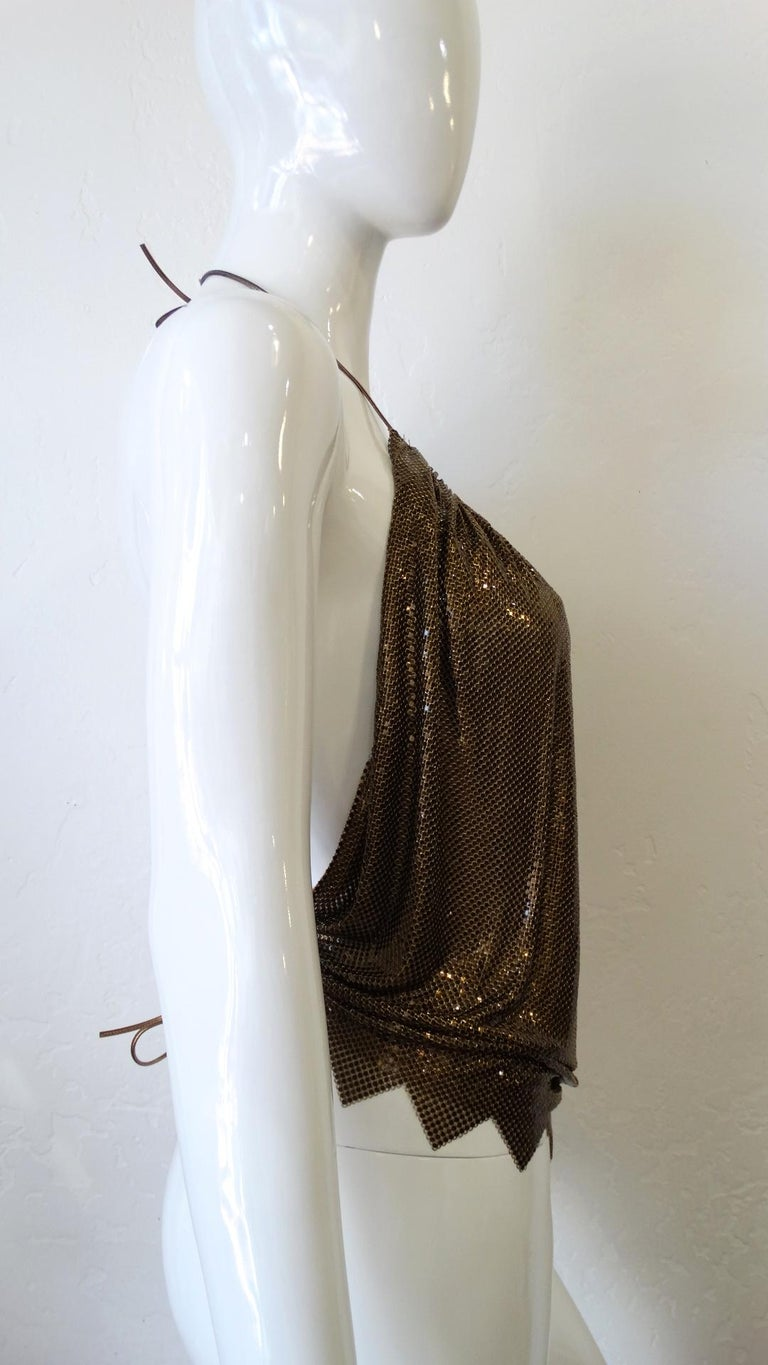 Bring The 70s Back With This Metal Mesh Backless Halter Top! By Whiting and Davis, this top features a gorgeous bronze color. Includes metallic bronze ties to the halter neck and to the back at the waist, with a ruched circular neckline and a