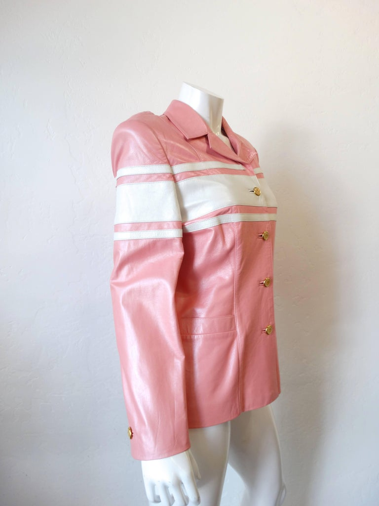 1980s Escada racing stripe jacket! Made of soft baby pink leather accented with white racing stripes. Gold metal and enamel emblem buttons up the front. Fully lined satin interior with kiss mark print! Marked a size 40.