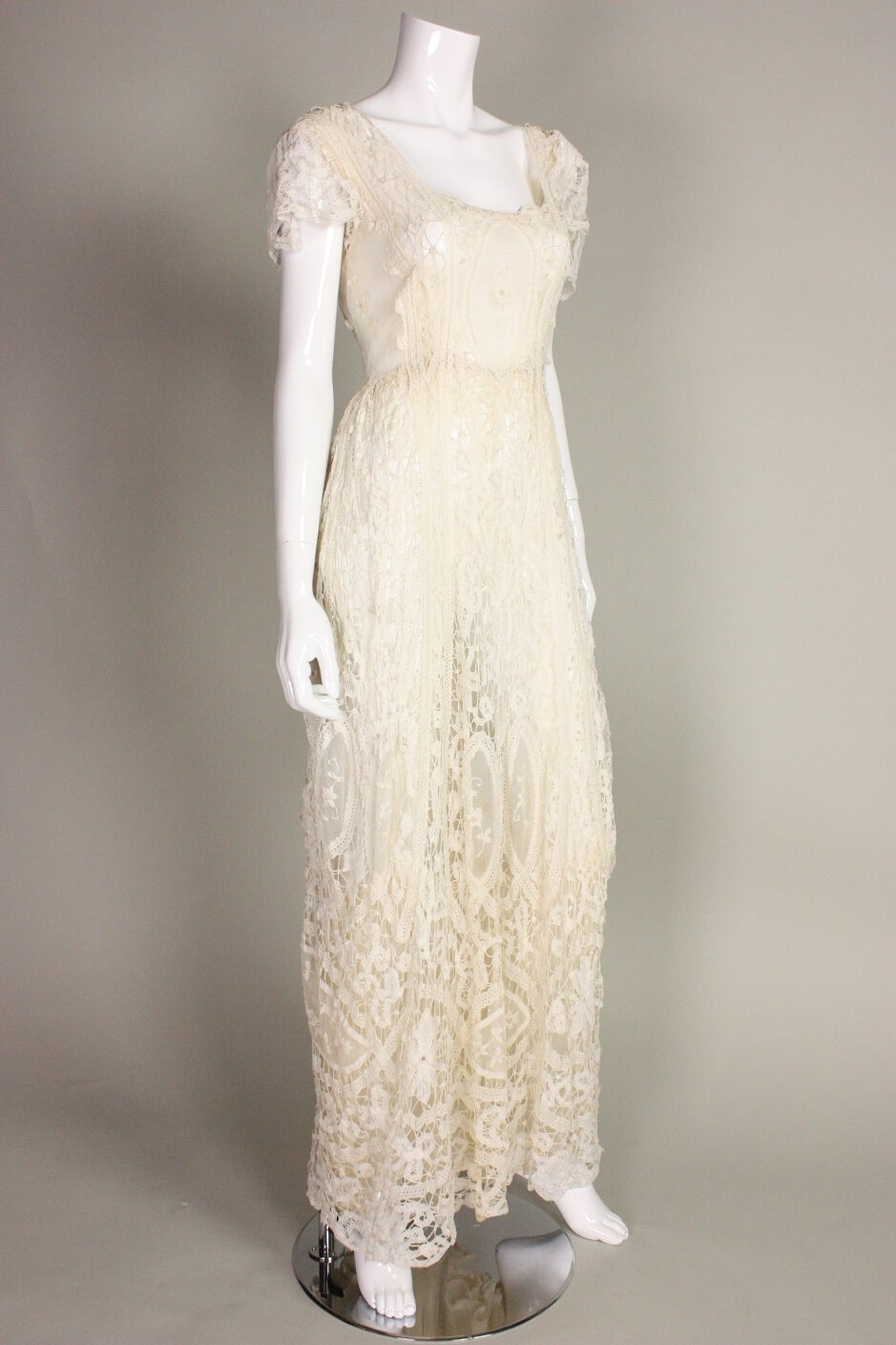 Beautiful gown dates to the Edwardian era and is made of ivory Battenburg lace.  Squared scoop neckline.  Lace is gathered at center lower back, just above the buttocks.  Short sleeves. Lined with a very fine silk. Closes in back with a series of