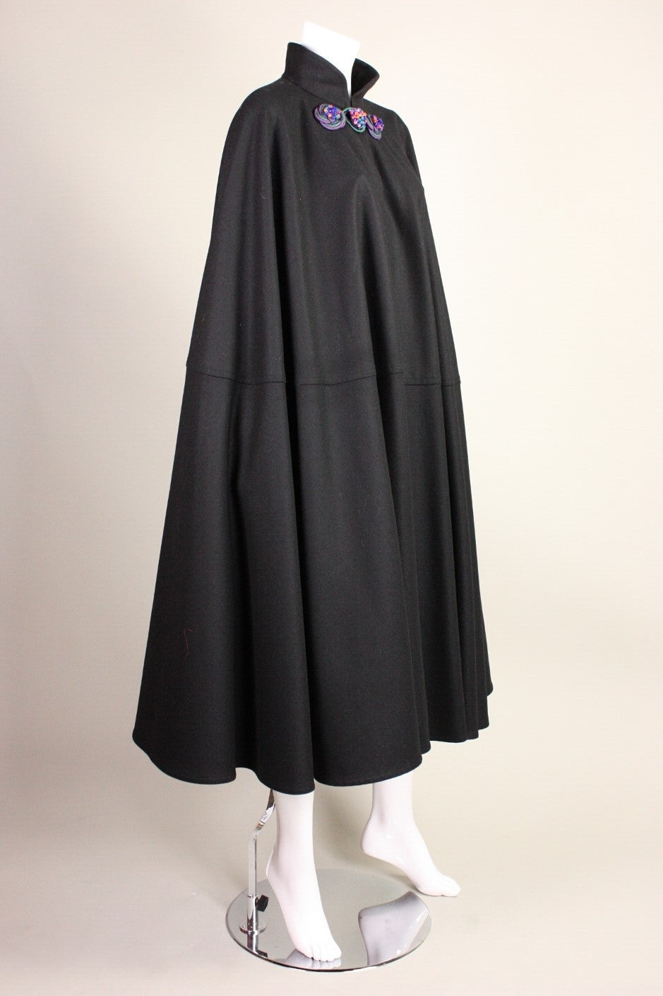 Vintage cape from Yves Saint Laurent dates to the late 1970's and is made of black wool with multicolor stone closure at center front neckline.  Stand collar.  Unlined.  Center front hook and eye closure behind frog fastener.