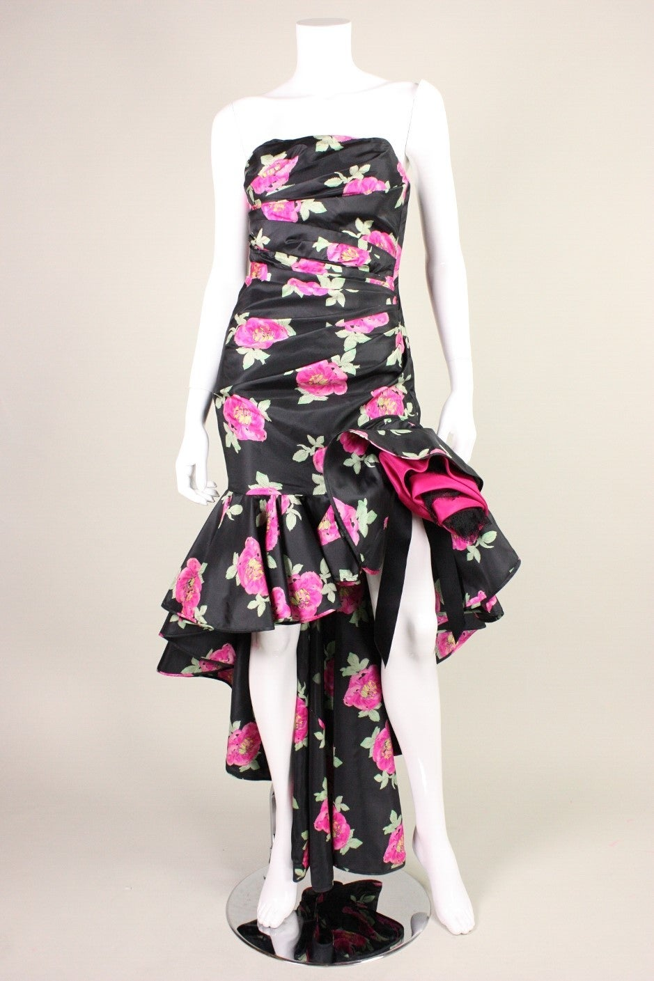 Flamenco-inspired evening dress from Emanuel Ungaro dates to the 1980's and is made of black silk taffeta with a pink floral print.  Front and back bodice are ruched on both sides.  Side zipper.  Fully lined.  Labeled a vintage size 8, but please