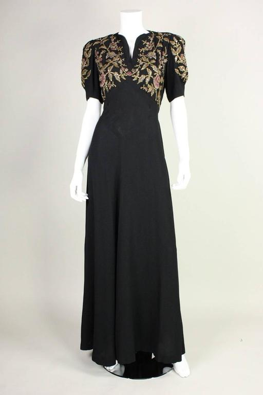 Vintage black crepe gown dates to the 1940's and has fabulous floral ornamentation on bust and sleeves.  Ornamentation includes pastel seed beads, larger brass-colored spherical bead highlights, and raised gold outlines. Bodice features v-neck and