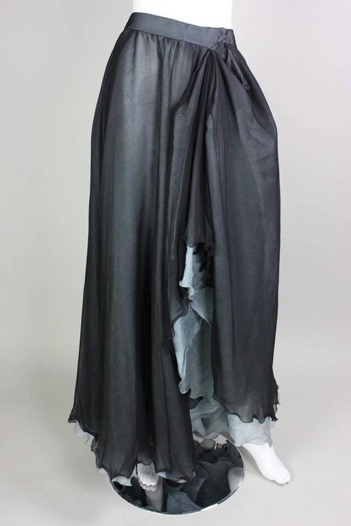 Vintage skirt from Giorgio Armani likely dates to the 1990's and is made of two layers of silk.  Under layer is a baby blue silk jacquard with a floral pattern.  Over layer appears to be black silk organza.  Side front of skirt has been stitched at