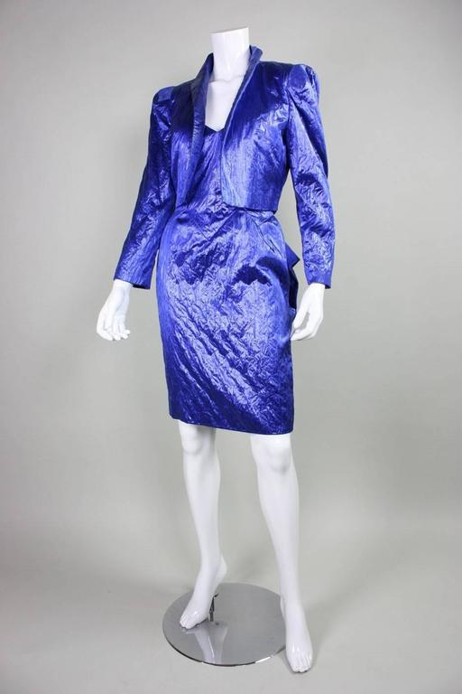 Vintage cocktail dress and jacket from Loris Azzaro is made of textured blue fabric and dates to the 1980's.  The dress has a jagged geometric neckline that is echoed in the waistline of the skirt.  Origami-like folding on the backside of the dress