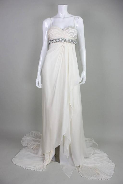 """Roberto Cavalli silk chiffon gown likely dates to the 1990' and is made of ivory silk chiffon with a rhinestone encrusted band under bust. One breast has gathered chiffon while the other is """"exposed"""" with quilted detailing. Fabric is gathered under"""