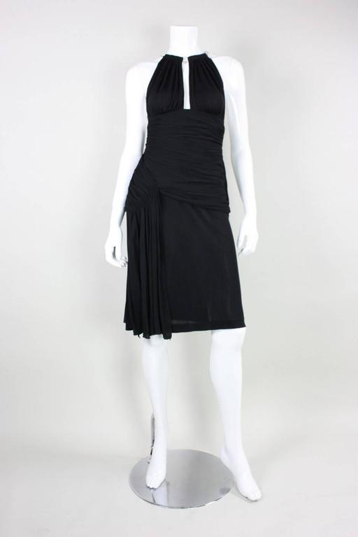 Vintage cocktail dress from Vicky Tiel dates to the 1980's. It is made of a black matte jersey with clear rhinestone straps.  Ruching throughout waist and hips.  Side zippered closure.  Lined through waist and hips, but not in skirt.