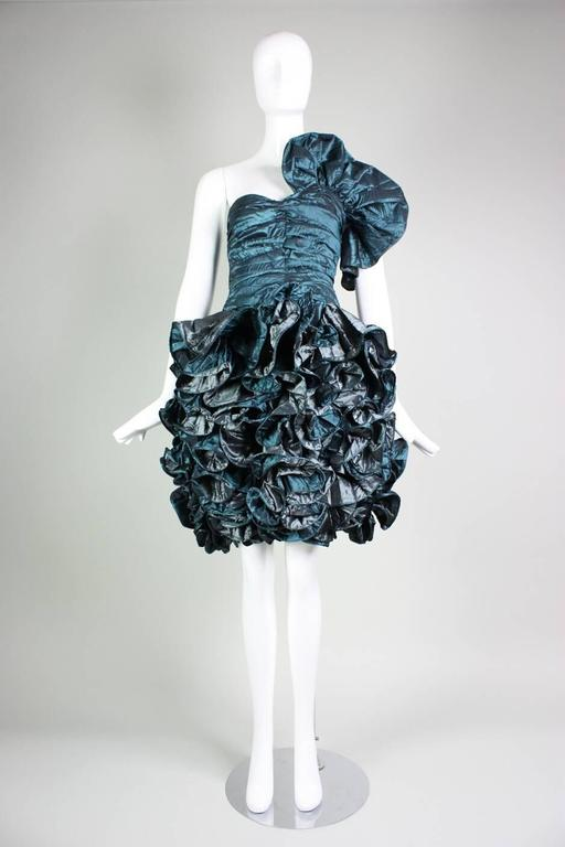 Vintage 1980's Christian Dior party dress dates to the 1980's and is made of iridescent green silk taffeta.  Fitted bodice is ruched throughout.  Skirt is fitted and features vertical ruffles.  Lined with a side zipper.  No size label though we