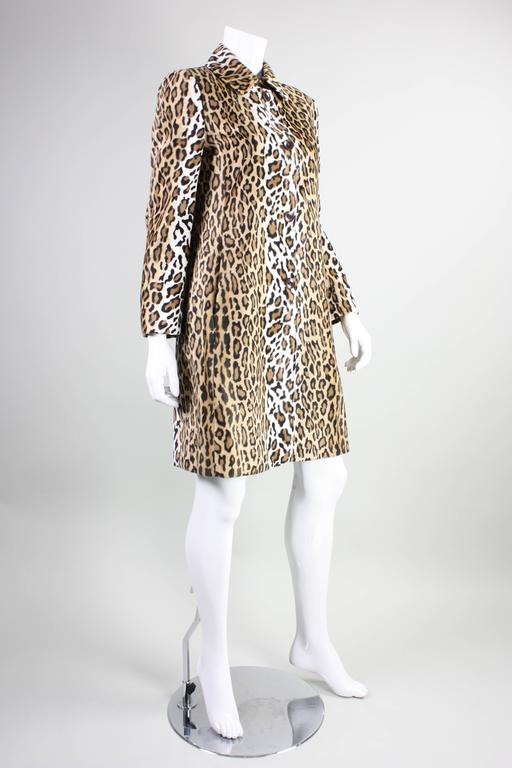 """Vintage Moschino Faux Leopard coat dates to the 1990's and is made of a poly-rayon blend.  Single breasted with turn down collar and four center front button closures.  Heart cutouts in buttons.  18 1/2"""" center back vent. Hip pockets in side seams."""