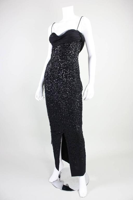 Vintage gown from Frank Starr likely dates to the late 1950's to early 1960's and is made of black crepe with black sequins sewn in a squiggle pattern that diminishes in density from top to bottom.  Gathered black chiffon band starts at right