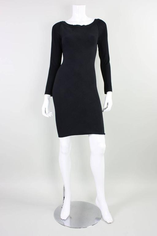 Vintage dress from Herve Leger dates to the 1990's and is made of a body-hugging houndstooth fabric front with plain black sleeves and back.  Boat neck front with v-neck back.  Center back zipper.  Unlined.  Labeled a FR 1, US