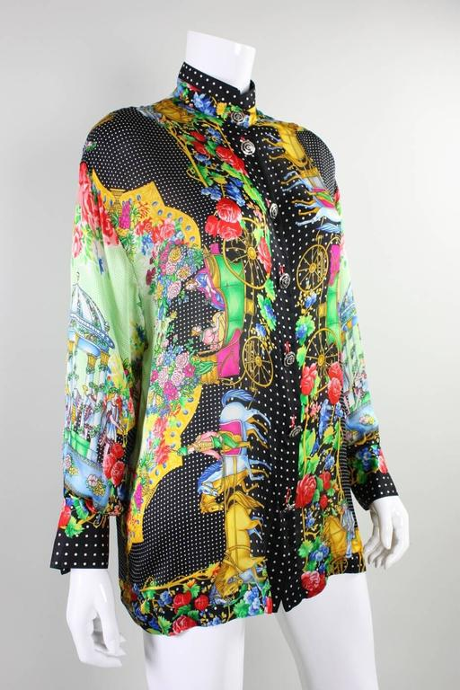 1990's Gianni Versace Couture blouse is made of silk charmeuse and dates to the 1990's. Blouse is multicolored and has a varying motifs. Center front silver-toned Medusa buttons with black enamel. Matching buttons at cuffs. Unlined.  Labeled size