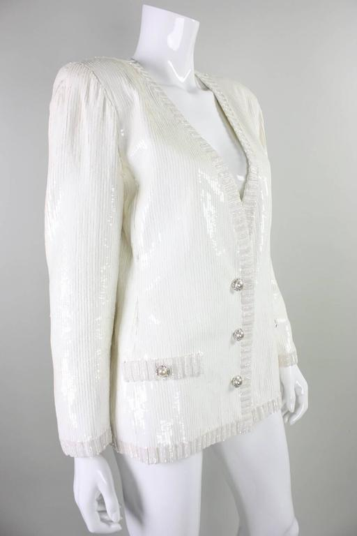 Vintage jacket from Bill Blass dates to the 1980's and features all over white sequins and faux pockets and faux button closures.  This jacket retailed at Amen Wardy.  Three hook and eye closures at center front waist.  Vintage size