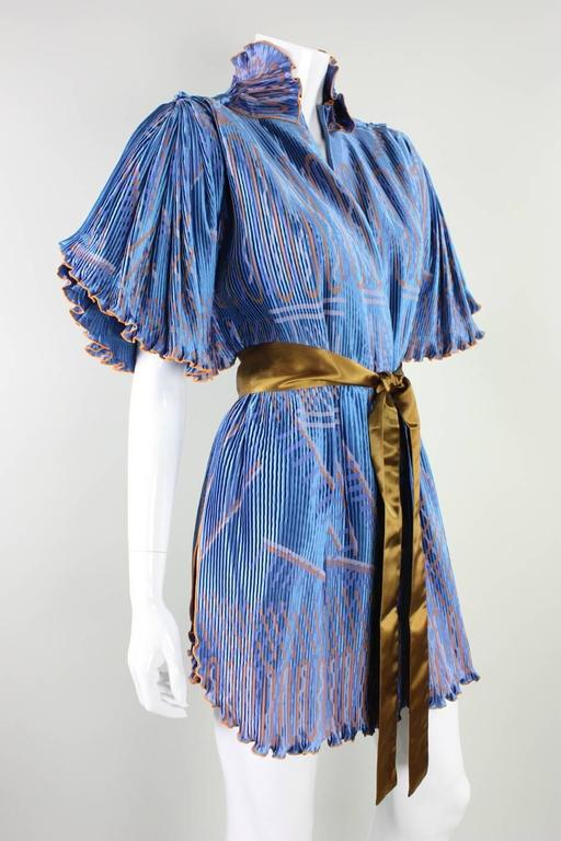 Vintage jacket from Zandra Rhodes dates to the 1970's through 1980's and is made of cornflower blue pleated rayon with an abstract pattern silkscreened throughout.  Detached sash also has the Zandra Rhodes label. Jacket is unlined and has no