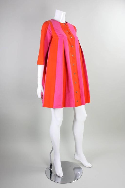 Vintage dress from Marimekko dates to the 1960's. It is made of cotton printed with orange and dark pink vertical stripes. Inverted pleats begin below front and back yokes. Dress can be worn with optional sash, which changes the dress' silhouette