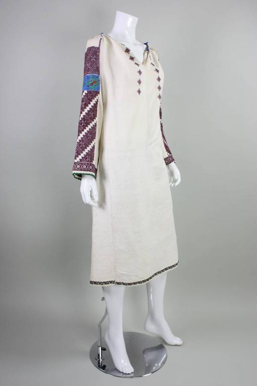 Vintage Eastern European folk dress likely dates to the 1930's or prior. It is made from cream linen with fine hand-embroidery on the sleeves, at hem, and front bust.  Underarm gussets. Unlined.  No closures.  No size label. Please refer to