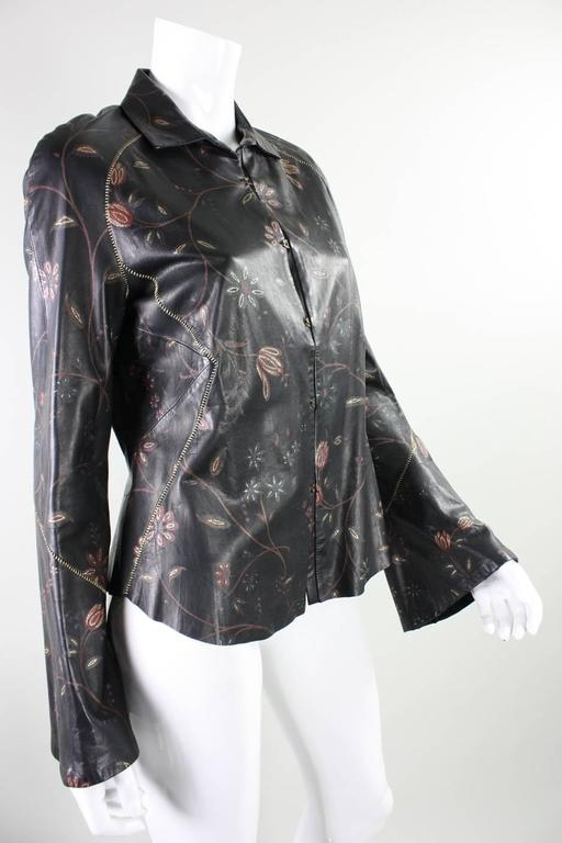 Roberto Cavalli buttery soft leather blouse or jacket has a rock & roll and western vibe.  It features slightly belled sleeves, gold-metallic stitching, and dark red and gold flowers.  Center front metal closures.  Partially lined.  Labeled size
