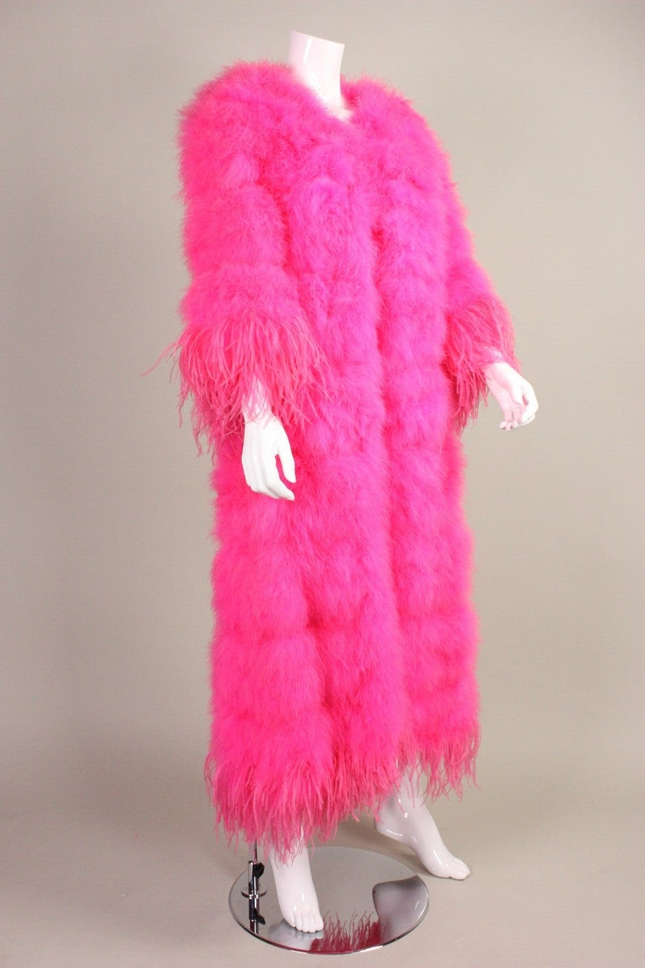 Vintage coat dates to the 1970's through 1980's and is made of hot pink marabou feathers with ostrich feather trim at the cuffs and hem.  Single hook closure at center front bust.  Fully lined.
