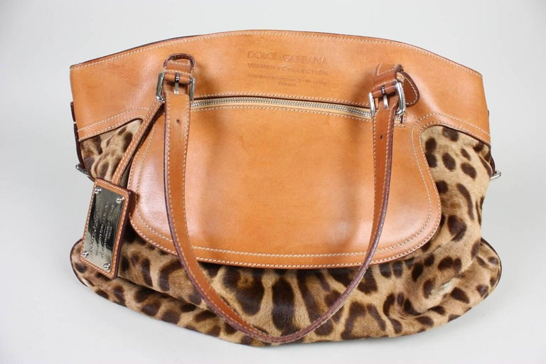 Gorgeous Dolce & Gabbana Miss Adventure weekender bag is made of leopard-print ponyhair and tan leather. It features silver-tone hardware, front zip pocket, interior zip pocket and top snap closure.  Adjustable shoulder and side straps. Matching