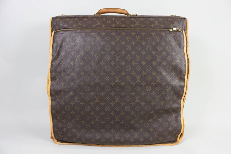 Vintage unisex Louis Vuitton garment carrier is made of brown and tan monogram coated canvas and dates to the 1990's.  It has brass hardware, tan vachetta leather trim, single rolled top handle and single exterior pocket with zip closure. Single