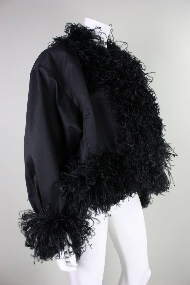 Vintage jacket from Yves Satin Laurent dates to the 1980's and is made of thick black cotton twill with flirty ostrich feather trim.  Dolman sleeves.  Fully lined.  No closures.  Side pockets at waist.  Padded shoulders.  Labeled a size 36, but this