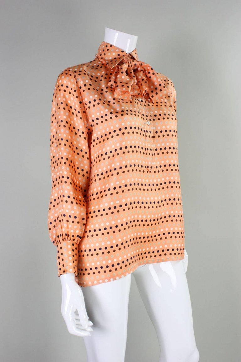 Vintage blouse from Valentino dates to the 1970's and retailed at I. Magnin.  It is made of melon-colored silk with polka-dots.  Detached sash can be worn around the neck, at the waist, in the hair or not at all.  Turn down collar with double button