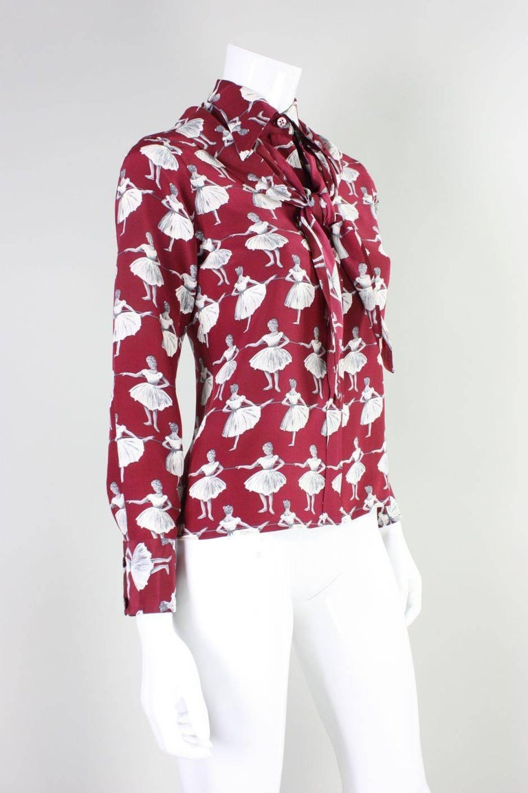 Vintage blouse from Valentino dates to the 1970's and is made of wine-colored silk that features a gorgeous ballerina print.  Blouse has wide turn-down collar, button front, and a detachable triangular scarf that can be worn in a variety of ways.