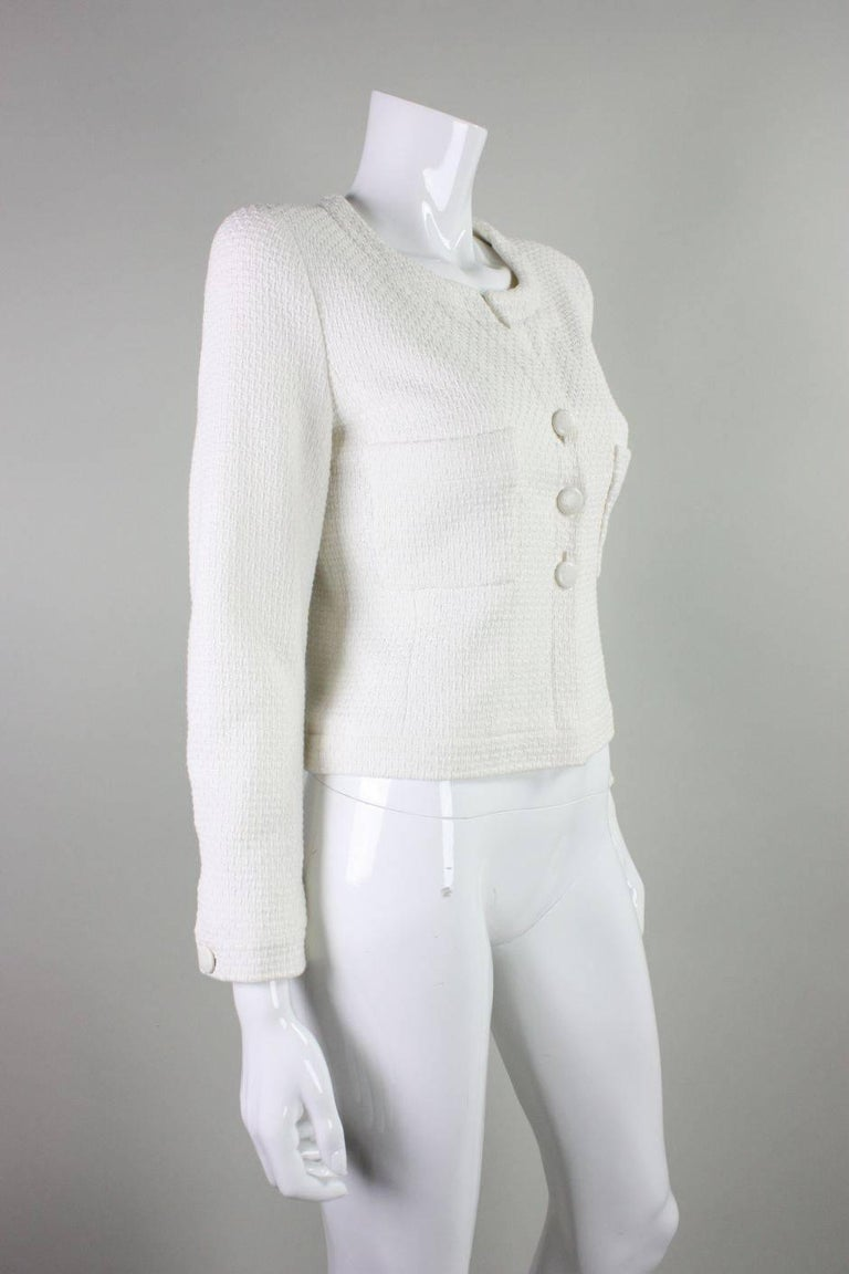 Vintage cropped jacket from Chanel dates to 1998 and is made of  white textured cotton.  Two patch breast pockets.  Three center front button closures.  Long sleeves with single buttoned cuffs.  Interior gold chain at waist.   Labeled a size