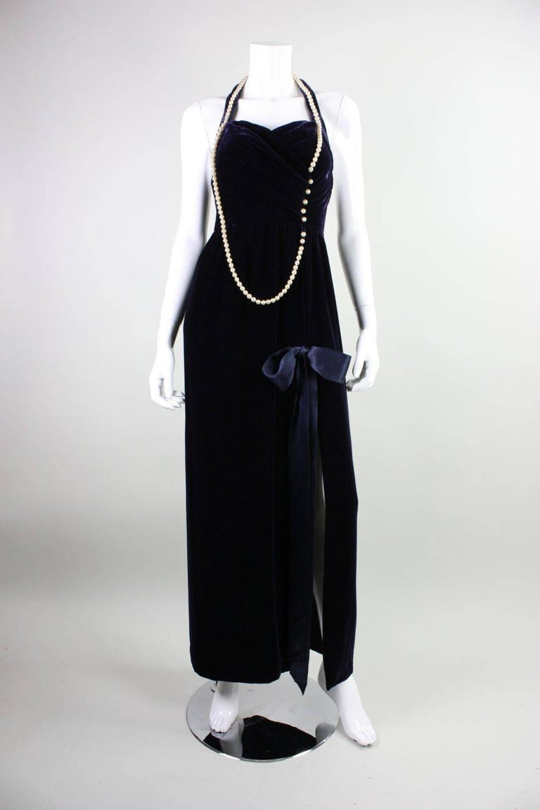 Vintage gown from Chanel was designed by Karl Lagerfeld in the 1990's.  It is made of midnight blue silk/rayon velvet with a strand of cream pearls that adorn the neckline and bodice.  Fitted bodice has halter sweetheart neckline and open back.