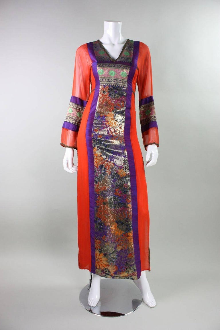 Vintage gown from English designer Thea Porter dates to the 1970's and retailed at Giorgio Beverly Hills.  It is made of a variety of fabrics including an orange silk chiffon, purple/blue silk shantung, and ethnic metallic jacquard.  V-neck and