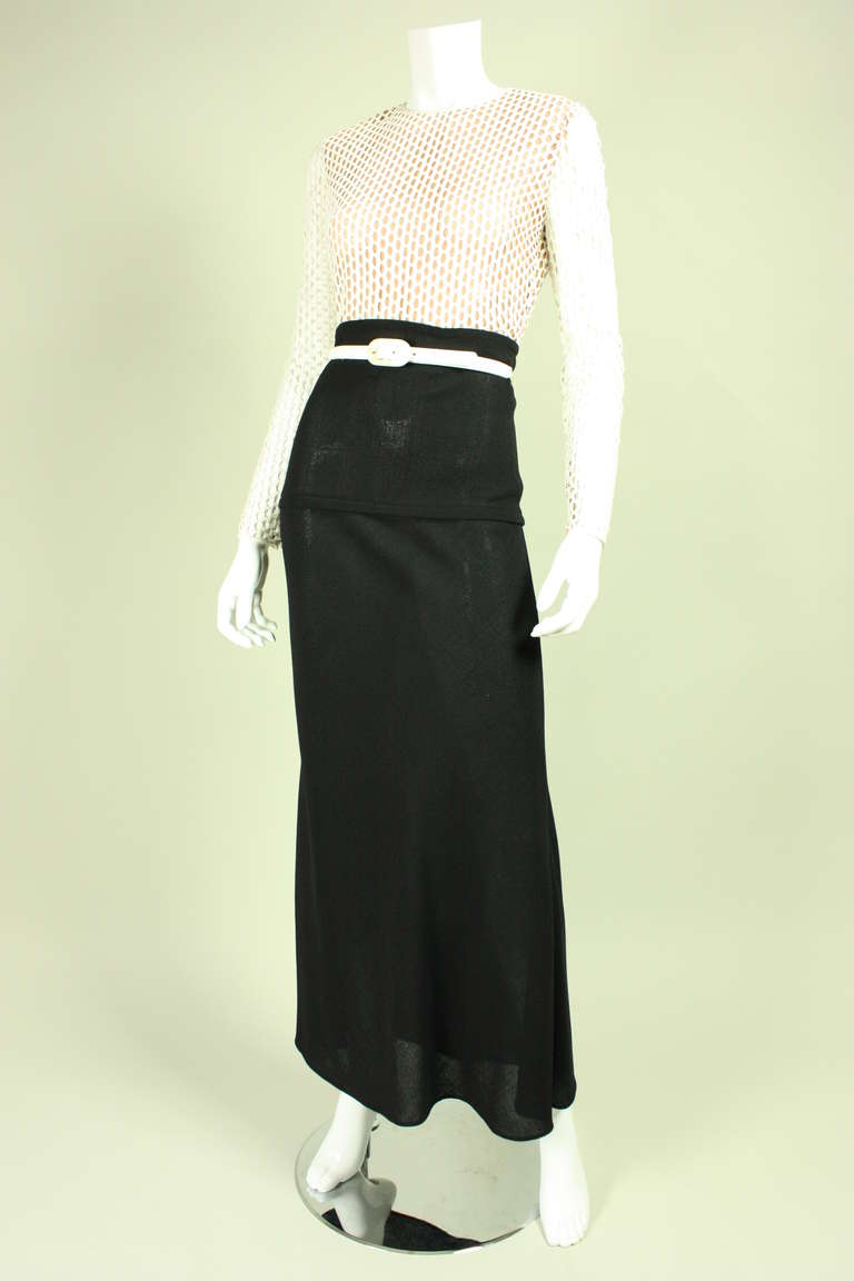 Vintage dress from American designer James Galanos dates to the 1970's.  The bodice is made of white fabric that is woven in an open fashion, but has a net backing against the body so that it is not transparent.  Skirt is made of fine black wool