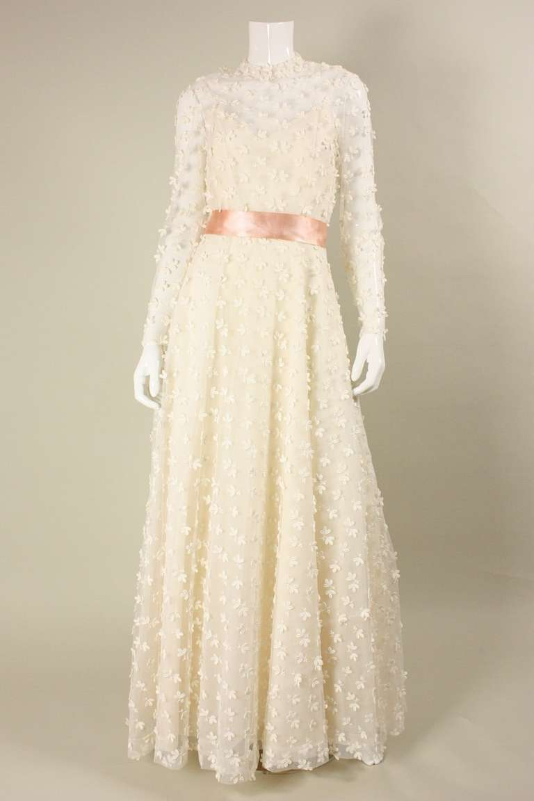 VIntage gown from Stavropoulos dates to the 1970's.  It is made of white netting with allover floral applique.  Fitted bodice has mock neck, long tapered sleeves, and keyhole opening at back.  Full skirt has underlayers that provide volume.  Center