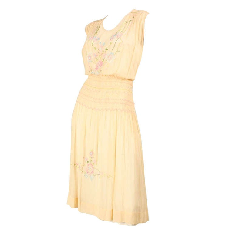 Vintage dress dates to the 1920's and is made of peach cotton voile.  The dainty embroidery is worked in varying shades of blue, green, pink, and white. The shoulders and hips are hand smocked and the bodice and skirt have hand embroidery and drawn