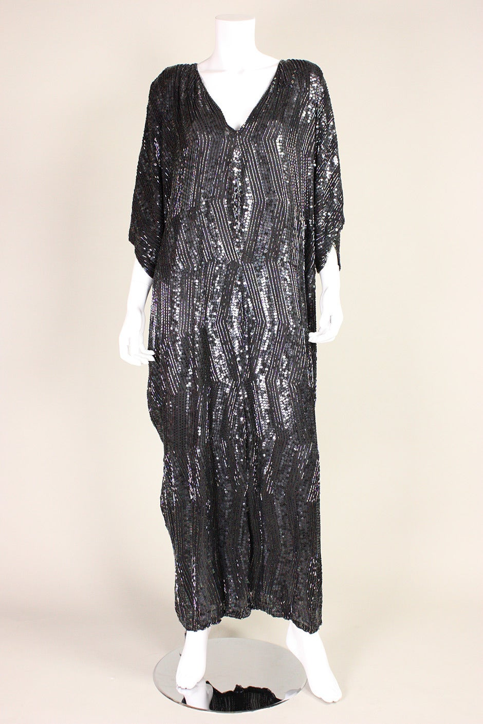 1980's Judith Ann caftan is made of black silk that is covered with sequins and bugle beads.  V-neck.  No closures.  Lined.