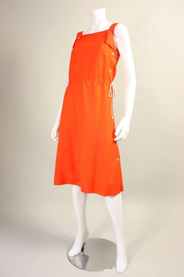 Vintage dress from Courreges dates to the 1970's.  It is made of brightly-colored orange linen with contrasting white drawstring and buttons.  Drawstring at waist can change the look of the dress.  Button closures.  Lined.