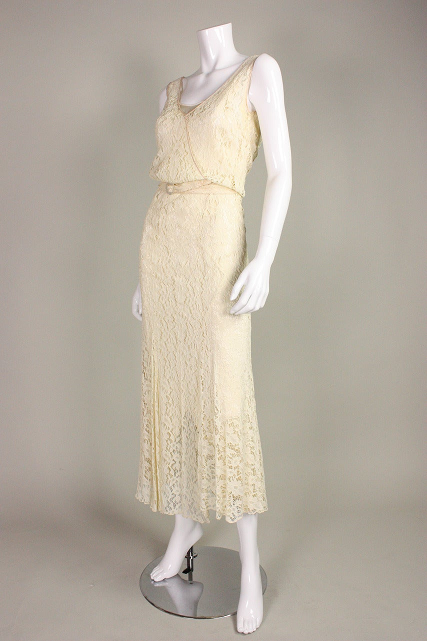 Vintage dress dates to the 1930's and is made of ivory-colored floral lace.  Sleeveless. Crisscross bodice results in a front v-neck.  Detached belt with mother of pearl buckle.  Side snap and hook and eye closure.  Unlined, but comes with